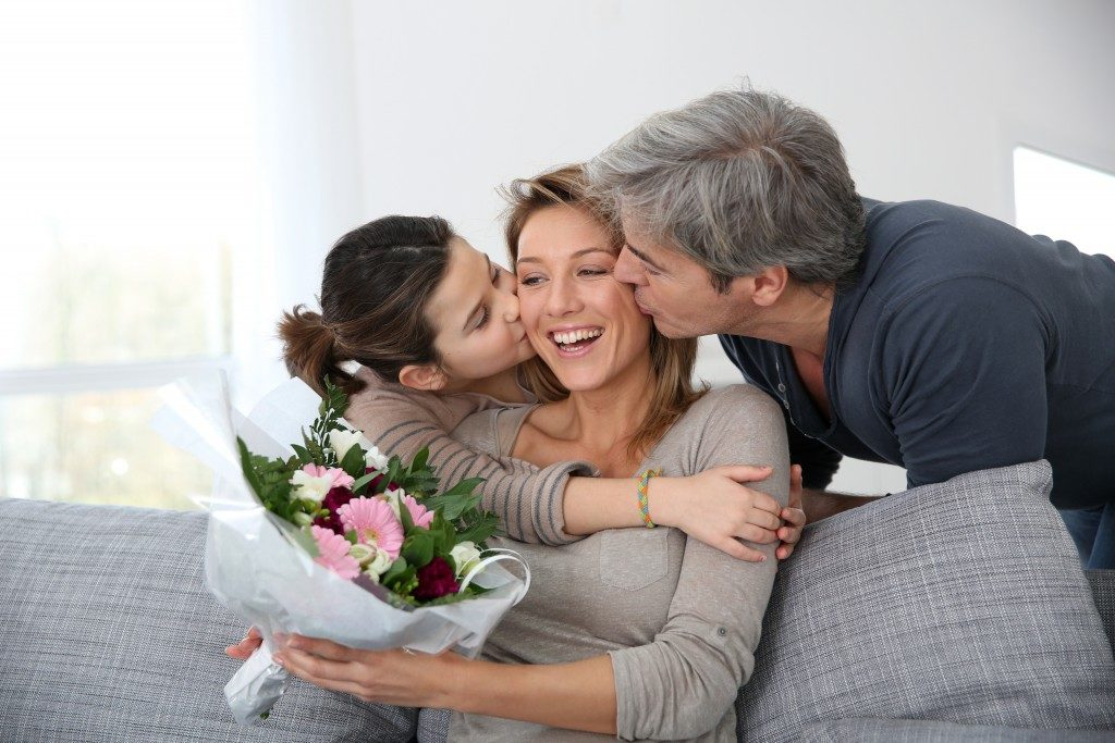 Mother holding flowers from husband and daughter
