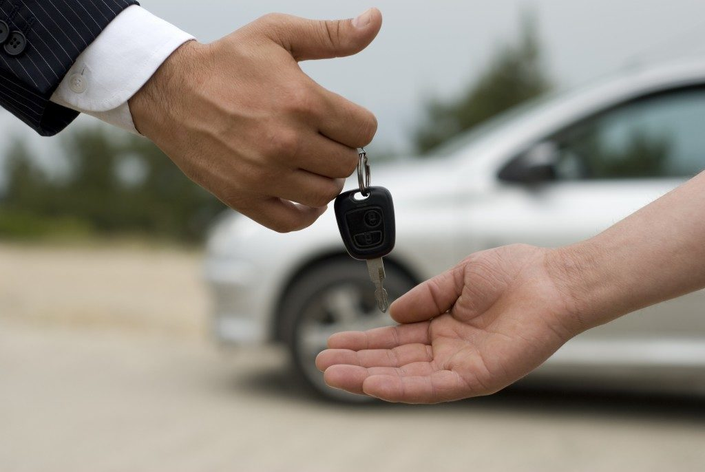 agent handing out car key to customer