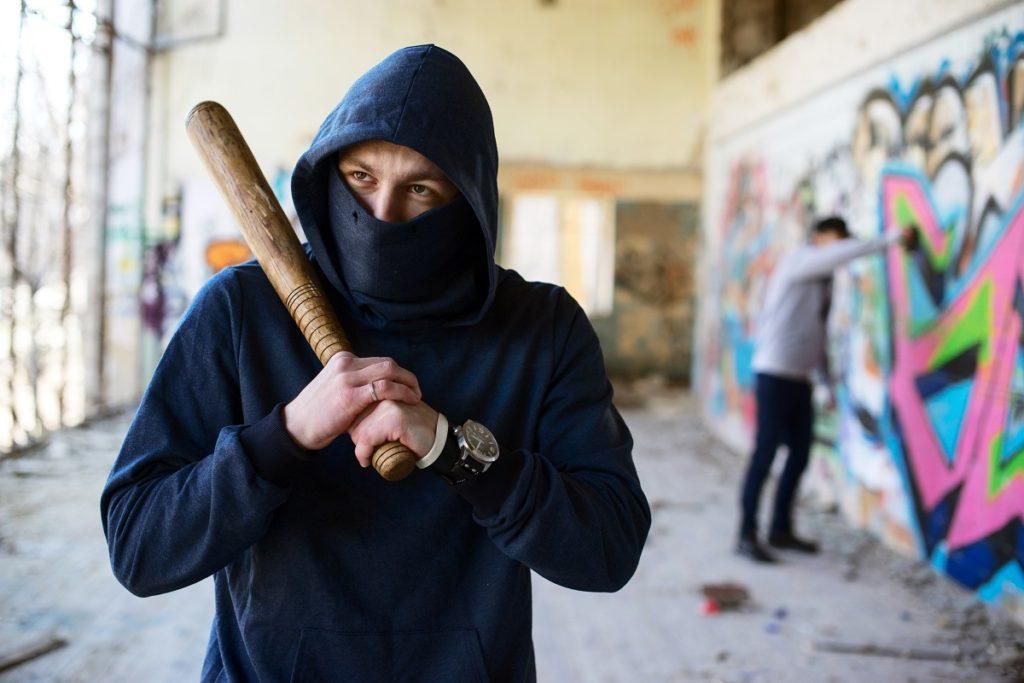 man wearing a hoodie holding a bat