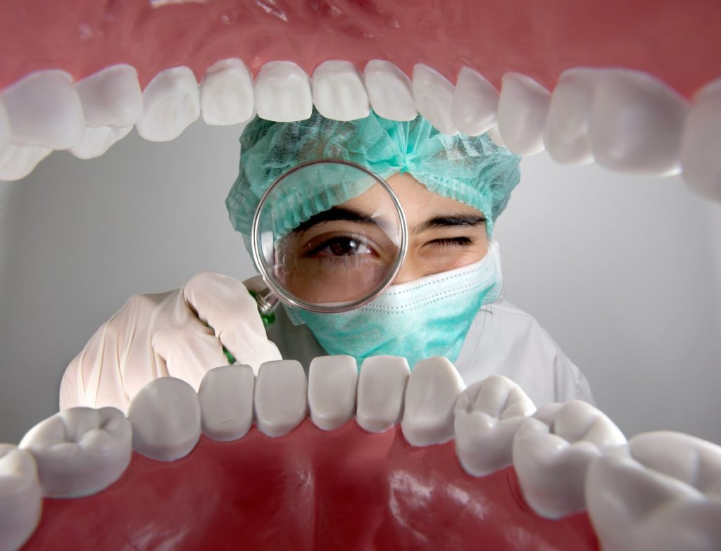 Dentist checking the teeth using magnifying glass
