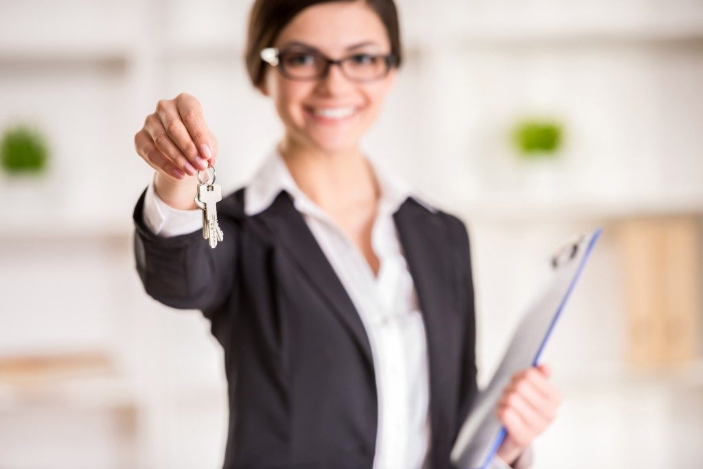 Realtor is holding the keys to an apartment to clients.
