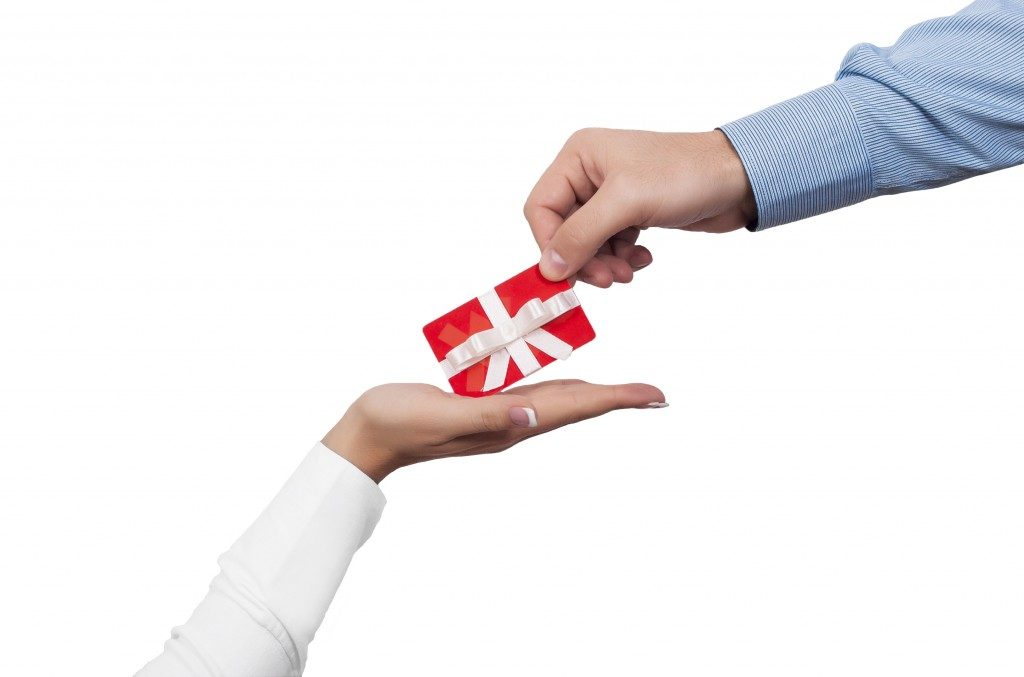 handing gift wrapped in red box