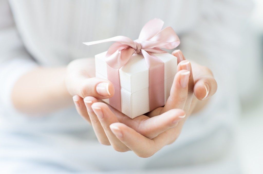 Close up shot of female hands holding a small gift wrapped with pink ribbon.
