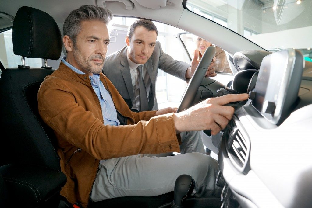 Client with car salesman looking at new car