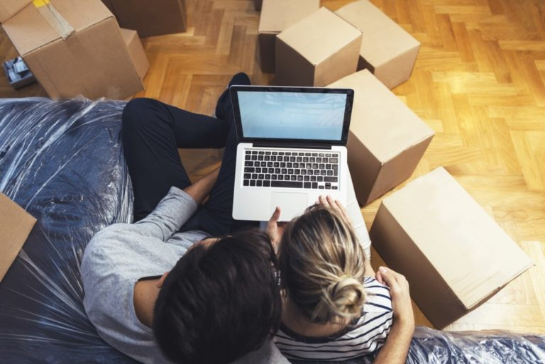 Couple looking at laptop while surrounded by boxes