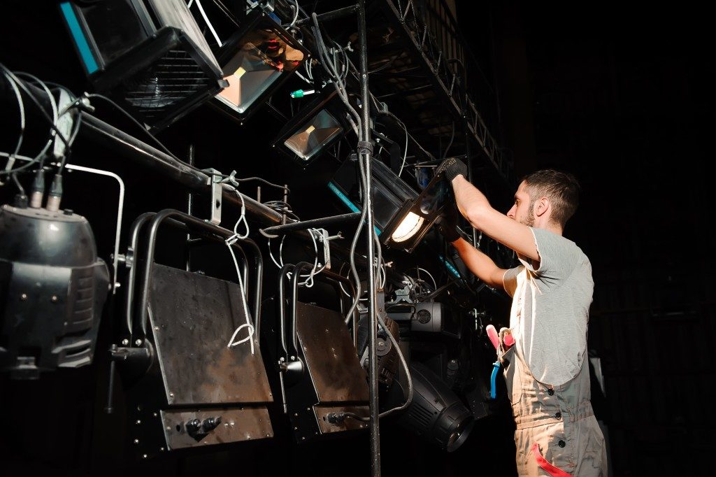 man setting up the stage lights
