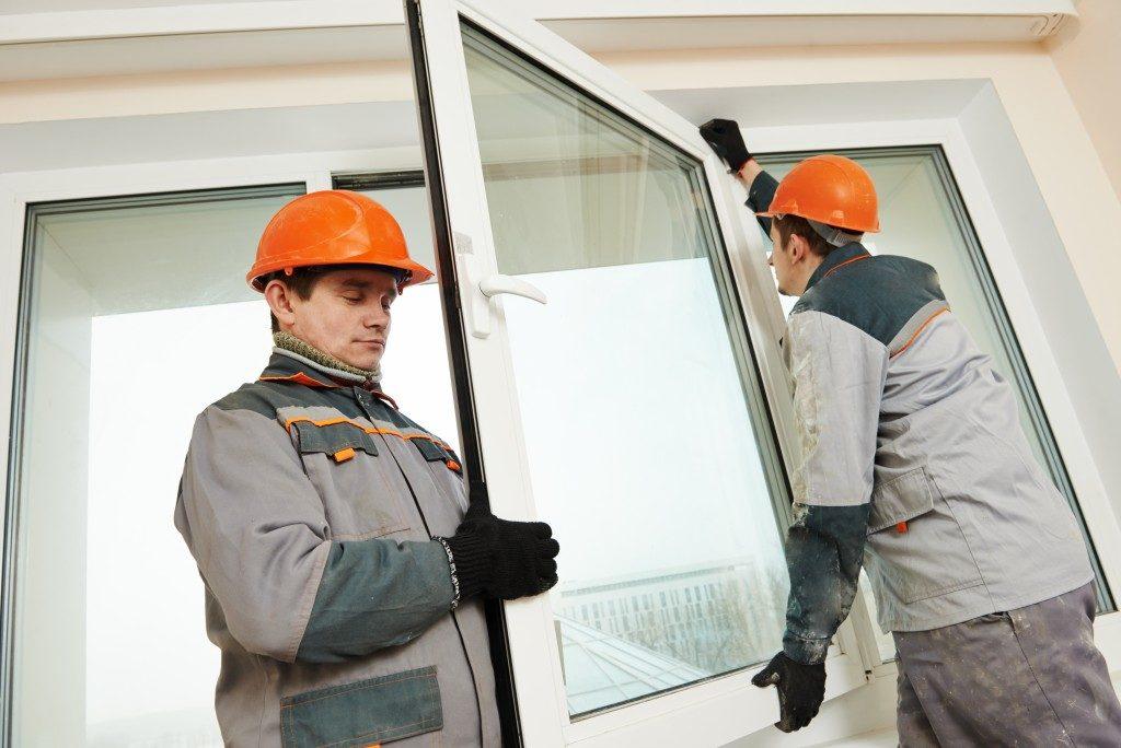 two handymen replacing a window