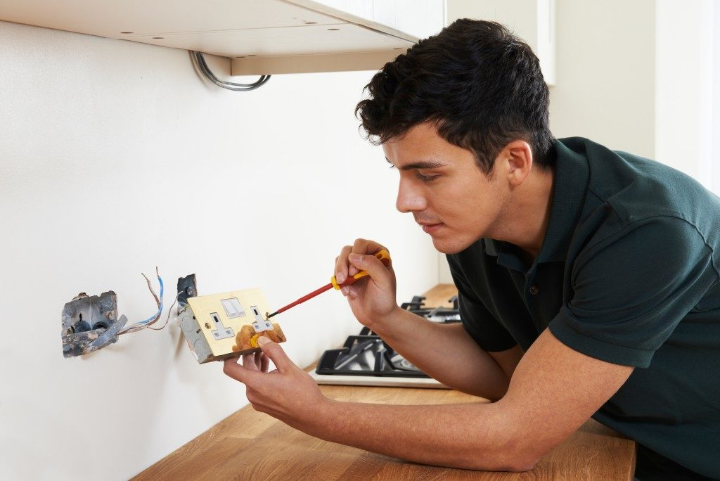 man fixing the outlet at home