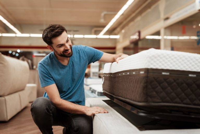 Man checking a new mattress in the mattress store