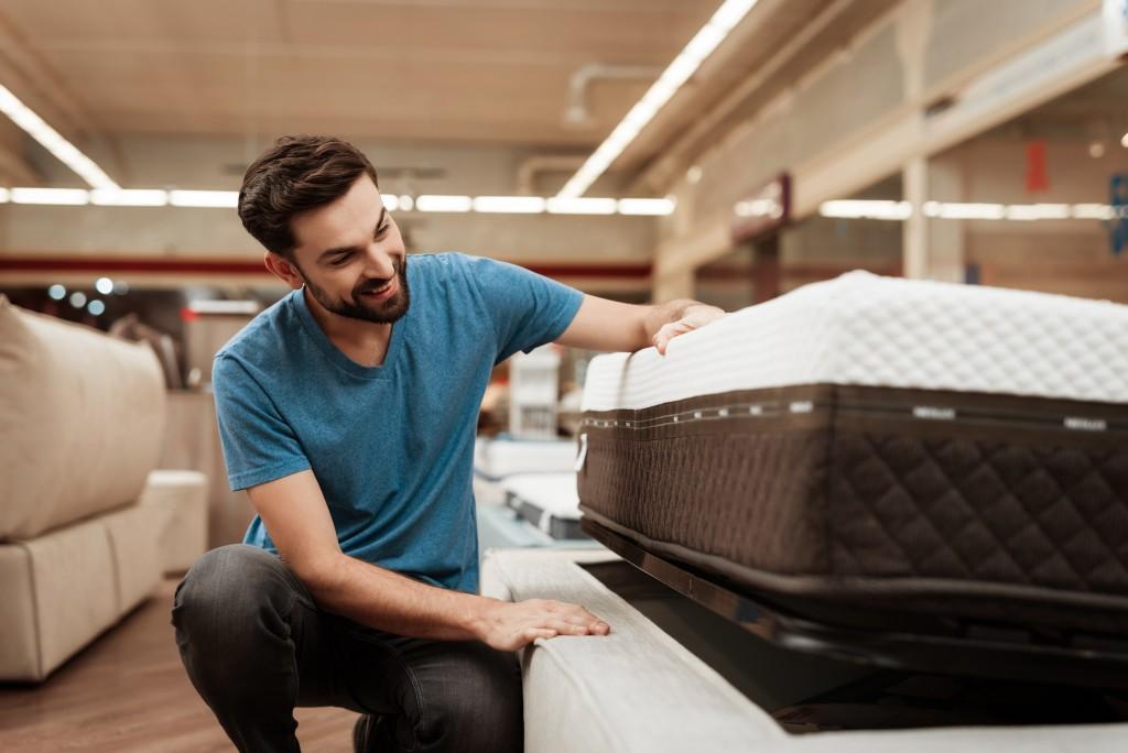 Man checking a new mattress in the mattress store