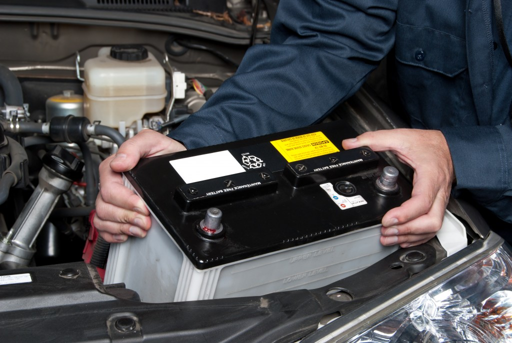 car mechanic replaces a battery