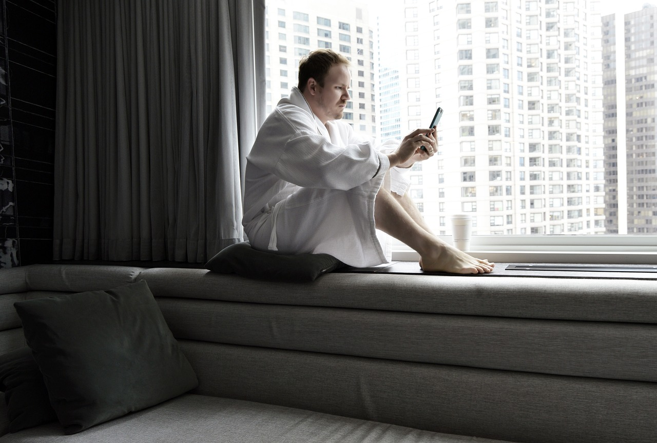 man sitting by the window in his room