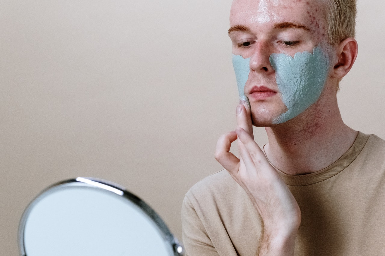 man applying a mask to his face