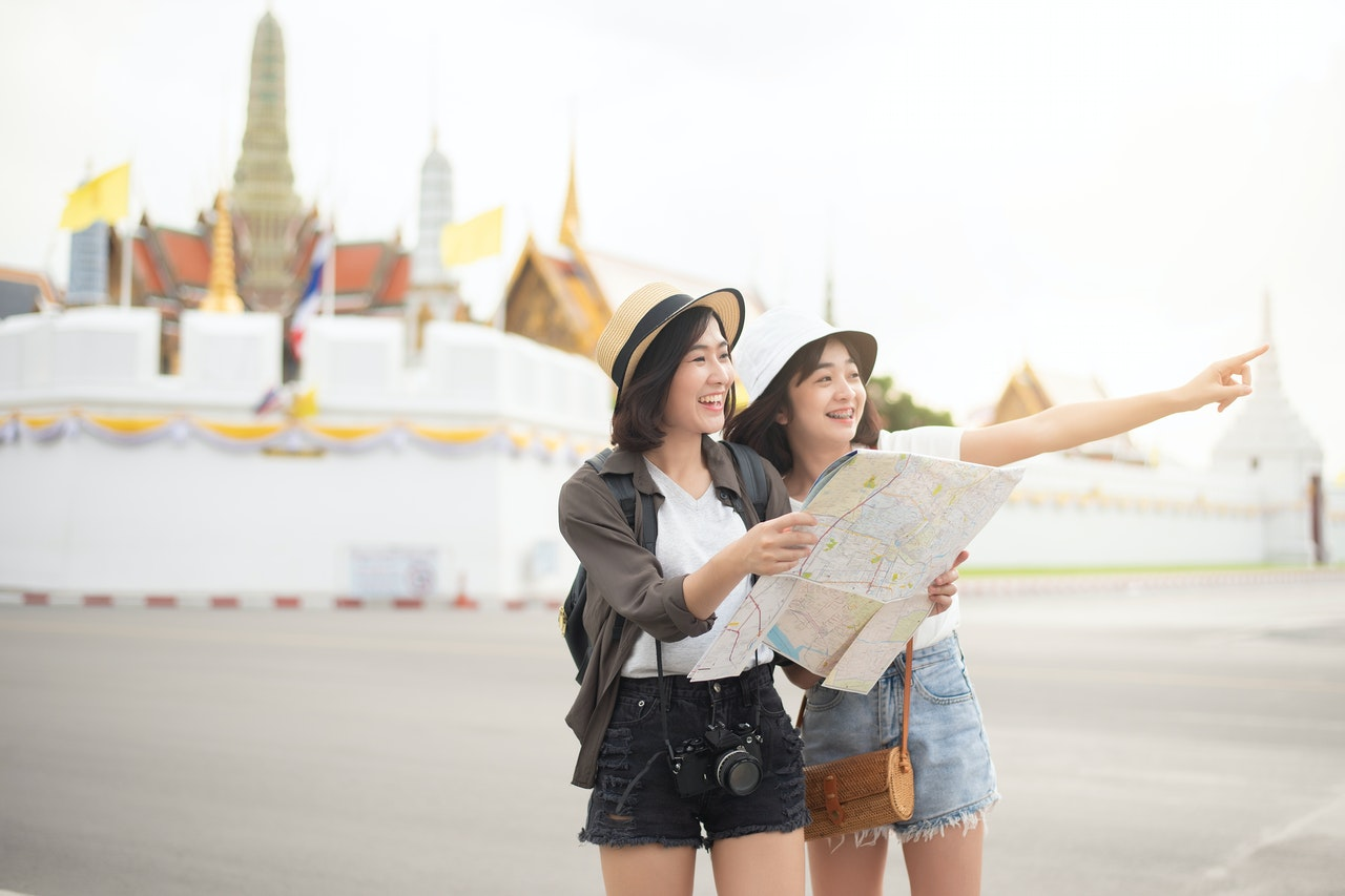 2 woman tourists holding map pointing