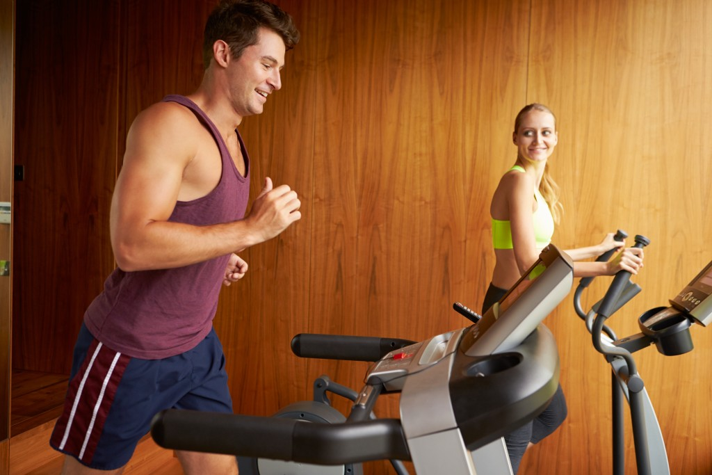 man and woman running on their treadmills