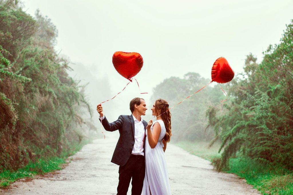 couple holding heart shaped balloons