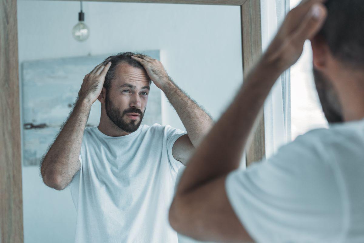 man touching hair looking at mirror