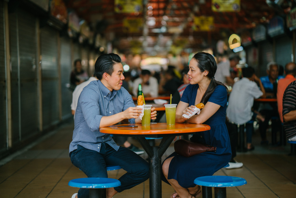 man and woman eating street food