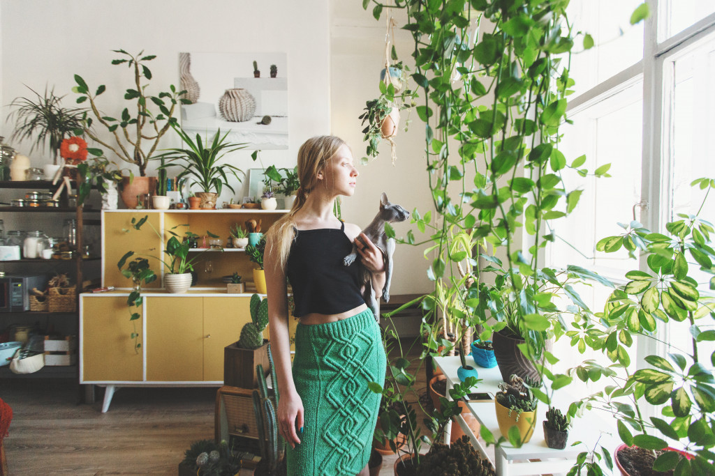 girl staring to a window with plants inside the room